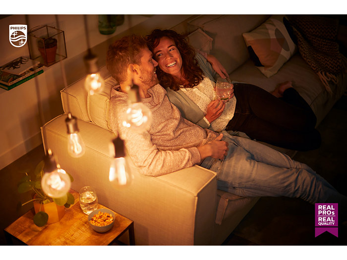 Couple looking t each other in a dark room with cozy lights