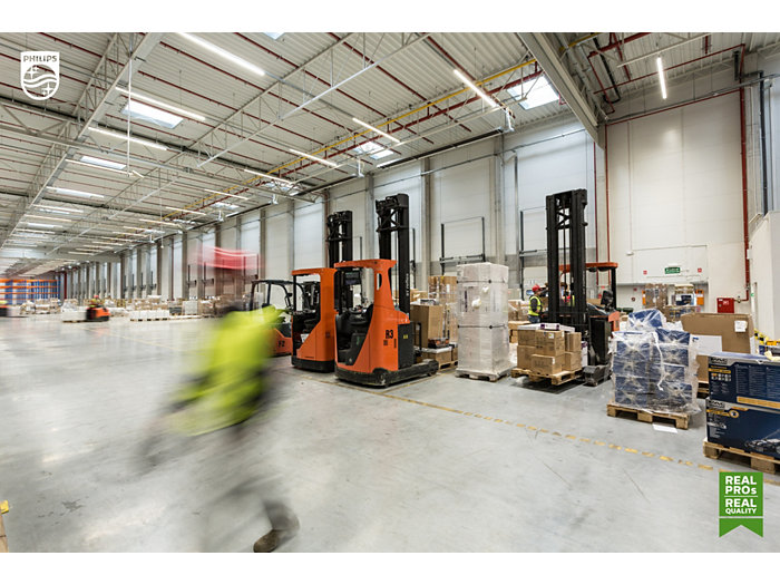 Stockroom with a forkliftruck and a worker in a warehouse