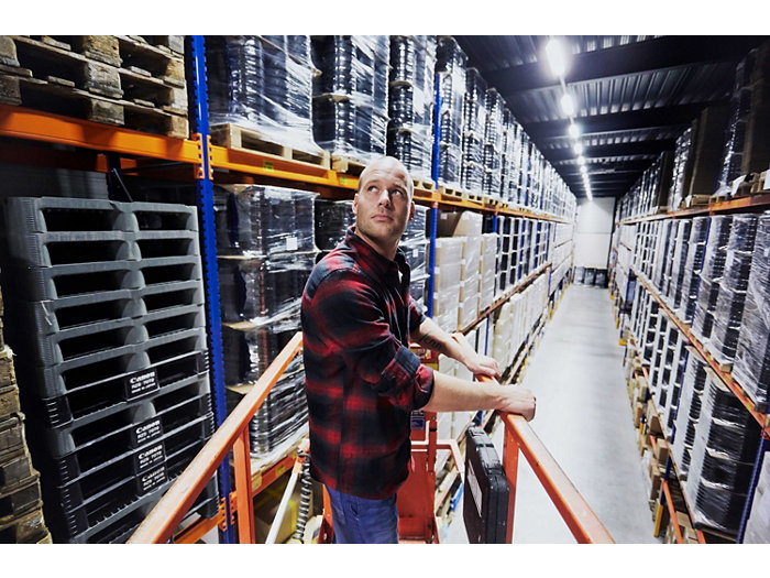 Application picture of MASTER LEDtube. Installer looking up in an industrial looking storage. Bold guy on a hydrolic haust in a red and black shirt and jeans. Pallets with product in the shelves.