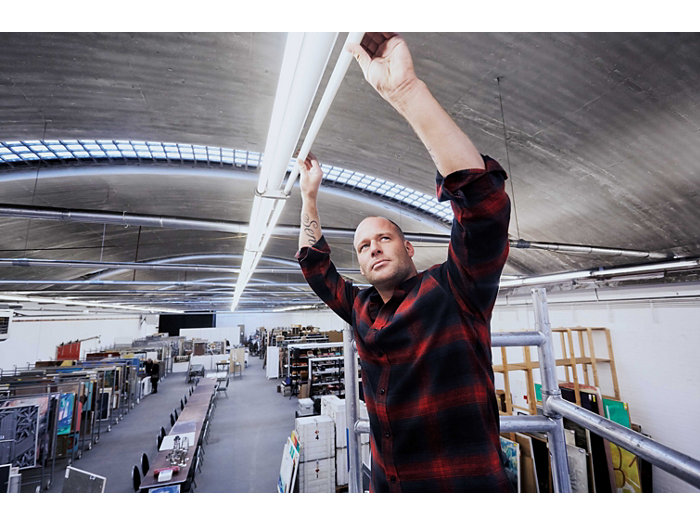 Application picture of MASTER LEDtube. Installer attaching the tube to the luminaire in an industrial looking art storage and workplace. Bold guy in a red and black shirt with tattoo on his right arm.